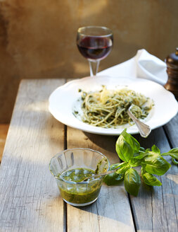 Glass of homemade basil pesto and basil leaves - KSWF001482
