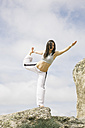 Woman doing yoga exercises on a mountain - ABZF000031