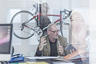 Businesspeople discussing in office, on carrying bike in background - ZEF004915