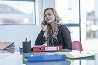 Portrait of blond woman telephoning with smartphone in an office - ZEF005077