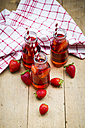 Three glass bottles of homemade strawberry lemonade - LVF003364