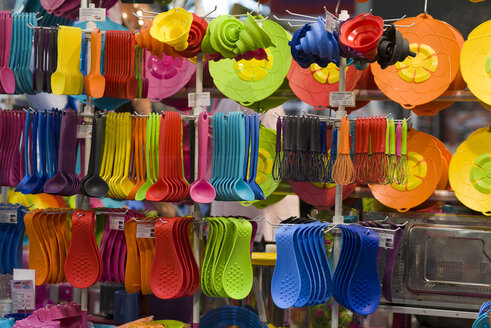 Colourful plastic cutlery and kitchen utensils in a shop - KLR000065