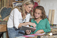 Mother and daughter doing crafts and using digital tablet in home garage - ZEF004858