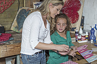 Mother and daughter doing crafts in home garage - ZEF004859