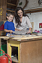 Mother and son doing crafts in home garage - ZEF004862
