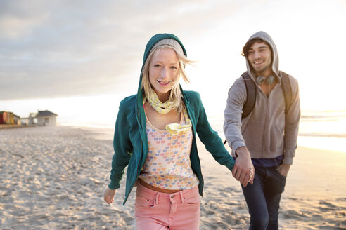 Young couple walking on beach at sunrise - TOYF000412