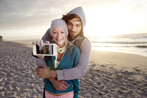 Young couple taking a selfie on beach at sunrise - TOYF000418