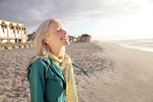 Smiling young woman on beach at sunrise with closed eyes - TOYF000430