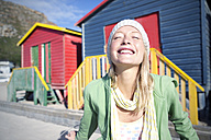 Happy young woman in front of colorful beach huts - TOYF000460