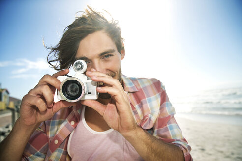 Young man taking picture on the beach - TOYF000481