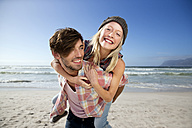 Young man carrying girlfriend piggyback on beach - TOYF000484