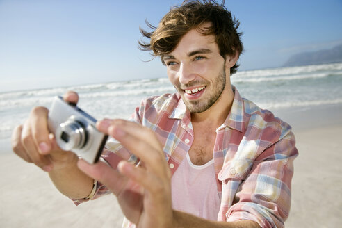 Young man taking picture on the beach - TOYF000492