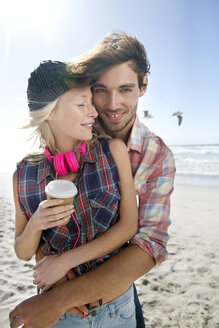 Happy young couple hugging on beach - TOYF000494