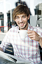 Portrait of smiling young man in a cafe - TOYF000521