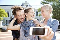 Happy friends outdoors taking a selfie - TOYF000614