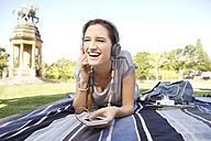 Young woman lying on blanket in park listening to music - TOYF000547