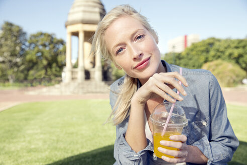 Young woman in park with soft drink - TOYF000550