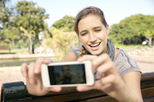Happy young woman on park bench taking a selfie - TOYF000559