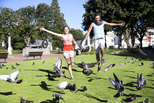 Enthusiastic young couple chasing pigeons in park - TOYF000571