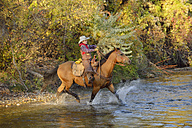 USA, Wyoming, young cowboy riding his horse across river - RUEF001589