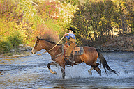 USA, Wyoming, young cowboy riding his horse across river - RUEF001592