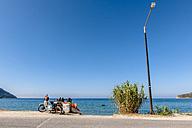 Greece, Corfu, Agios Georgios, moped and street lamp at the ocean - EGBF000084