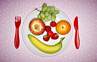 Plate with fruits building funny face and red plastic cutlery on pink cloth - KSWF001508