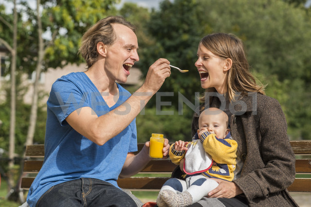 Happy family with baby food on bench - FBF000394 - Frank Blum/Westend61