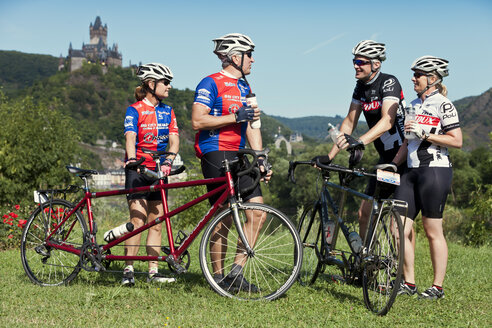 Germany, Rhineland-Palatinate, US American couples standing in nature in front of Eltz Castle with their tandems - MF002076