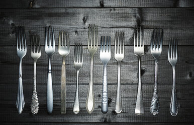 Row of different forks on wood - KSWF001524