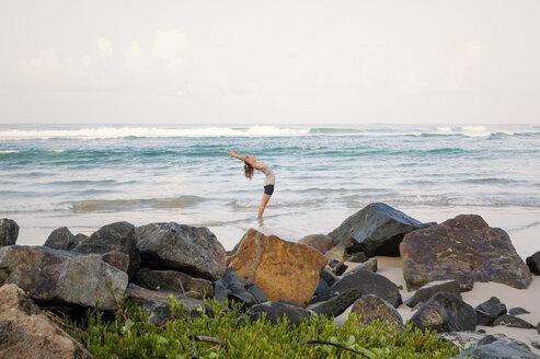 Sri Lanka, Kabalana, young woman practicing yoga at the coast - WV000748