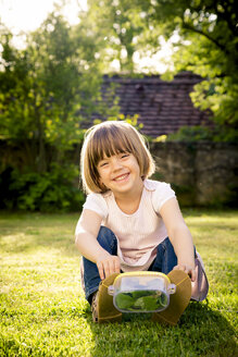 Little girl with insect can sitting on a meadow - LVF003399