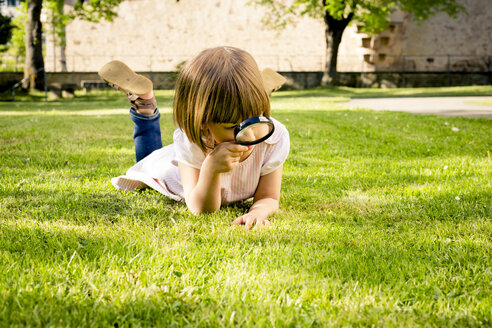 Little girl lying on a meadow using magnifying glass - LVF003402