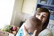 Young mother holding baby in kitchen - STKF001215