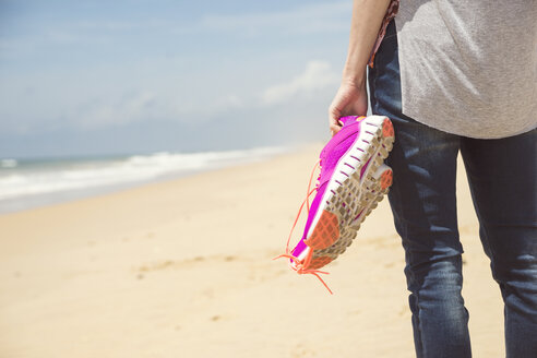 Portugal, Faro, woman on the beach holding pink sneakers in her hand - CHPF000144