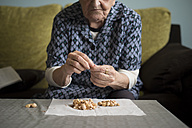 Aged woman eating pistachios at home - RAEF000187