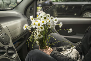 Woman sitting with flowers in car - RIBF000060