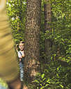 Girl in forest behind tree trunk - UUF004260