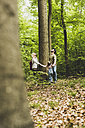 Family in forest standing around tree trunk looking up - UUF004269