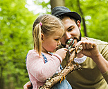 Girl with father in forest examining branch with magnifier - UUF004272