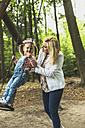 Mother holding daughter on swing - UUF004277
