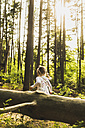 Girl in forest behind log - UUF004290