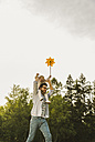 Father carrying daughter with paper windmill on shoulders - UUF004305