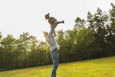 Father lifting up daughter on meadow - UUF004310