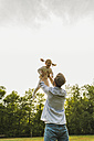 Father lifting up daughter on meadow - UUF004311