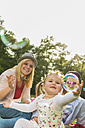 Happy family catching soap bubbles - UUF004317