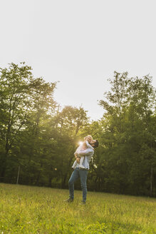 Father lifting up daughter on meadow - UUF004322