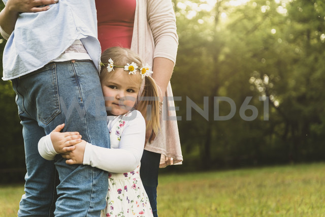 Girl embracing father's leg on meadow - UUF004324