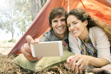 South Africa, happy couple lying in tent taking a selfie - TOYF000677