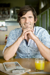 Portrait of smiling man in a cafe - TOYF000688